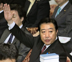 衆院予算委で答弁のため手を挙げる野田首相(26日午前)=共同