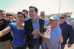SYRIZAのツィプラス党首はベネズエラのチャベス大統領を信奉している(6月8日、アテネの造船所を訪れた同党首=中央)=ロイター