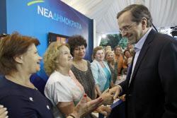 NDのサマラス党首は1月にモスクワを訪問した(6月11日、アテネで支援者と握手する同党首=右)=ロイター