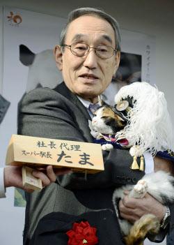 和歌山電鉄の社長代理に昇格した三毛猫「たま」と同社の小嶋光信社長(5日、和歌山県紀の川市の貴志駅)=共同