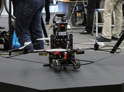 図1 自律飛行する小型監視ロボット。汎用の飛行台車にレーザーセンサーやカメラ、LED照明の他、通信機器や制御用のコンピューターを搭載した