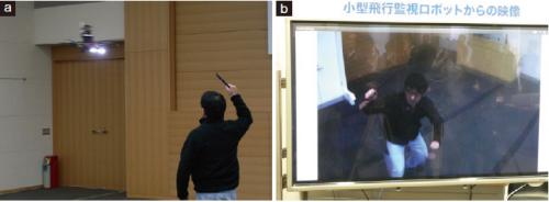 図3 不審者を監視するデモンストレーションの様子。不審者に対して顔が分かるように正面から写真を撮影する(a)。(b)は撮影した映像。数m程度の距離を保って飛ぶので、反撃を受けにくい