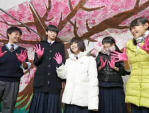 神戸の中学生と一緒にピンクの手形で桜の木を描いた大船渡中学校の森田さんと及川さん(左から2人、3人目)=17日午前、神戸市中央区