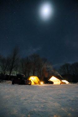 月明かりに照らされる雪景色のキャンプ場。冬の澄んだ空気は天体観測にも向いている