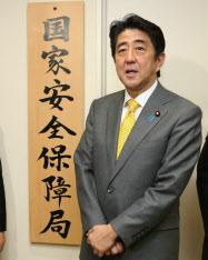 国家安全保障局の看板を設置し、記者の質問に答える安倍首相(7日)