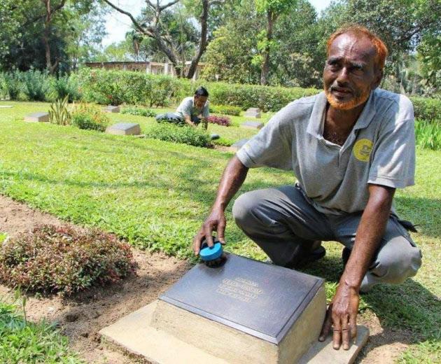 日本兵の墓碑を丁寧に磨くビルフレッド・ゴンサルゲスさん(バングラデシュ中部コミラ)
