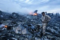 ウクライナ東部のマレーシア航空機墜落現場で、散乱し炎を上げる残骸=17日(タス=共同)