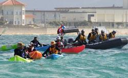普天間代替施設の建設に向け始まったブイの設置作業に抗議するカヌーと警戒する海上保安庁のボート=右端=(14日、辺野古沖)=共同