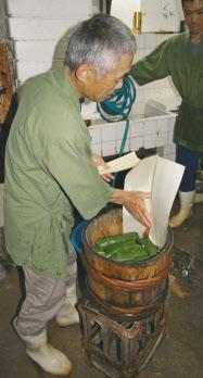 あせの葉で包み、おけに並べて10日ほど発酵させる(和歌山市内の弥助寿司)