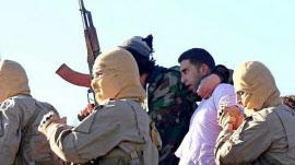 イスラム国の兵士らにかつがれるヨルダン軍のパイロット=AP
