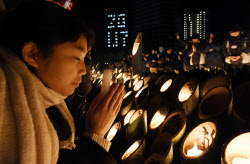 阪神大震災の発生時刻に犠牲者の冥福を祈り黙とうする人たち(17日午前5時46分、神戸市中央区の東遊園地)