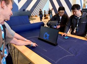 タッチパッドの機能を持たせた布地を指でなぞってスマホを操作する(画面の青い線は指の軌跡)