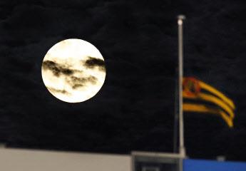 甲子園球場の上空に浮かんだ今年最大となる満月「スーパームーン」。右は中村勝広GMを悼み、半旗で掲げられた阪神の球団旗=共同
