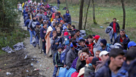 列車で到着した後、ハンガリーとの国境に向かう移民ら(16日、クロアチア)=ロイター