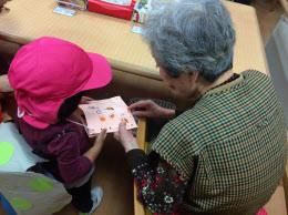 3歳の園児が作ったバッグを見せてもらうデイケア利用の高齢者(横浜市のココファン日吉)