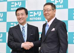 ニトリHDの次期社長に決まり、握手する白井副社長(左)と会長になる似鳥社長(26日、東京都北区)