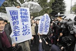 関西電力高浜原発3、4号機の運転を差し止める仮処分決定で、垂れ幕を掲げる弁護士ら(9日午後、大津地裁前)=共同