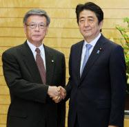 和解案受け入れを表明し、翁長知事(左)と握手する安倍首相(4日)