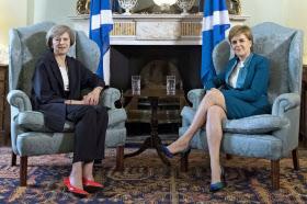 会談に臨むメイ首相(左)とスコットランド行政府のスタージョン首相(15日、エディンバラ)=AP
