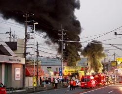 東京電力の関連施設から上がる黒煙(12日午後5時23分、埼玉県新座市)=共同