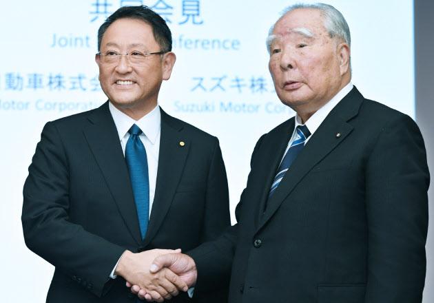 握手する豊田章男社長(左)と鈴木修会長(12日、東京都文京区)