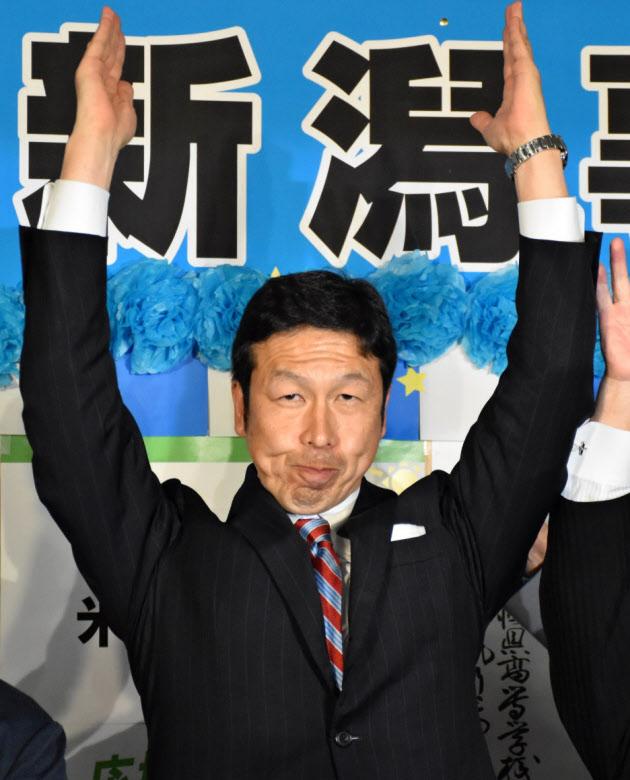 当選を決め、万歳する米山氏(16日、新潟市中央区)