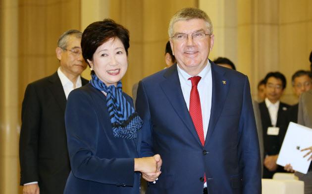 会談を前に握手するIOCのバッハ会長(右)と東京都の小池知事(18日午後、都庁)