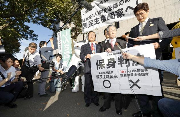 判決を受け、記者の質問に答える原告側弁護士ら(18日、東京高裁前)=共同