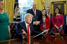 3日、金融規制の緩和に向けた大統領令に署名するトランプ米大統領=ロイター