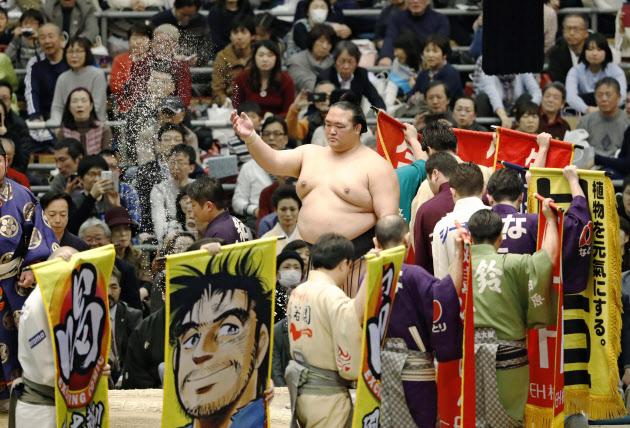 多くの懸賞の垂れ幕が回る土俵で、塩をまく新横綱稀勢の里関=12日、大阪市のエディオンアリーナ大阪