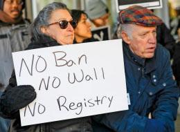 米移民税関捜査局の前で「入国禁止に反対」などと書かれたプラカードを持ち、新大統領令に反対する人たち(16日、シカゴ)=ロイター