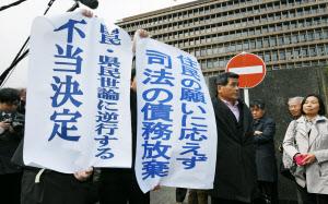 「不当決定」などと書かれた垂れ幕を掲げる住民側の弁護士ら(28日午後、大阪高裁前)