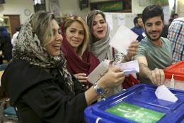 19日、首都テヘランで投票する市民ら=AP