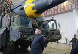 核・ミサイル開発に巨額をつぎ込む一方で前線の兵士の食糧事情は悪化している(5月、ミサイル実験に立ち会う金正恩氏)=AP