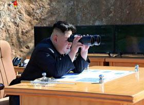 朝鮮中央テレビが4日放映した、ミサイルの発射実験に立ち会った金委員長の写真=共同