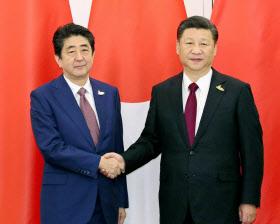 会談前に握手する安倍首相(左)と中国の習近平国家主席(8日、ドイツ・ハンブルク)=代表撮影・共同