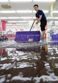 局地的な大雨で浸水した家電量販店で、たまった雨水をかき出す従業員(16日午後、北海道小樽市)