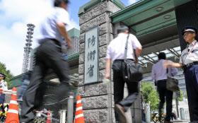防衛省に入る職員ら(28日午前、東京都新宿区)