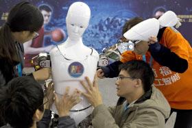 ロボットコンペに参加した中国の学生ら。中国政府はAIで中国が世界を主導するために支援体制を強化すると発表した=AP