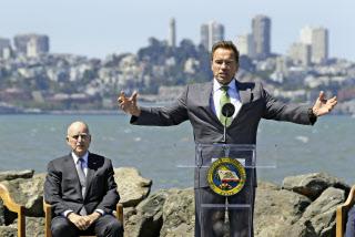 排出量取引制度延長の署名式に参加したカリフォルニア州のブラウン知事(左)とシュワルツネガー前知事(7月25日、サンフランシスコ)=AP
