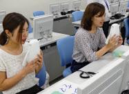 ロボットに英語で話しかける学生(神戸学院大学)