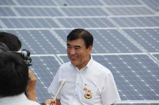 太陽光パネルをバックに取材にこたえる沢田氏