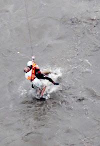 ヘリコプターでつり上げられ、救助される男性(30日午後4時43分、埼玉県新座市の柳瀬川)=共同