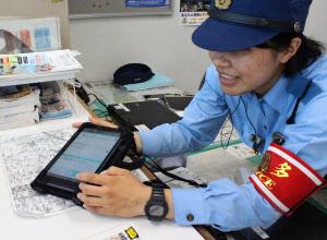タブレットを使って説明する博多駅前交番の警察官(福岡市博多区)