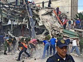 倒壊した建物で生存者を探す人々(19日、メキシコシティ)=AP
