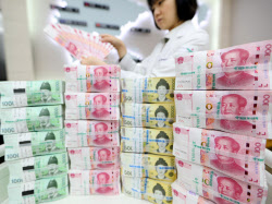 10日、韓国・ソウルの銀行に積まれた韓国のウォンと中国の人民元の紙幣=聯合・共同