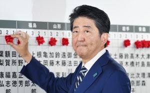 当選のバラをつける安倍首相(22日午後、自民党本部)