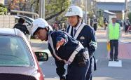 通学路付近で取り締まりをする警察官(26日、愛知県岩倉市)