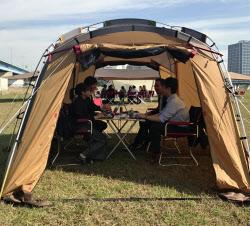 テントの中で打ち合わせをするオフィスワーカーたち(2日、川崎市)
