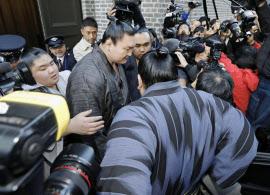 鳥取県警の参考人聴取を受けた福岡市内のホテルから出て、車に乗り込む白鵬(奥中央、28日)=共同